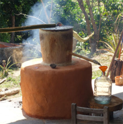 Second distillation in the Filipino still. Note the tree-trunk upper chamber.